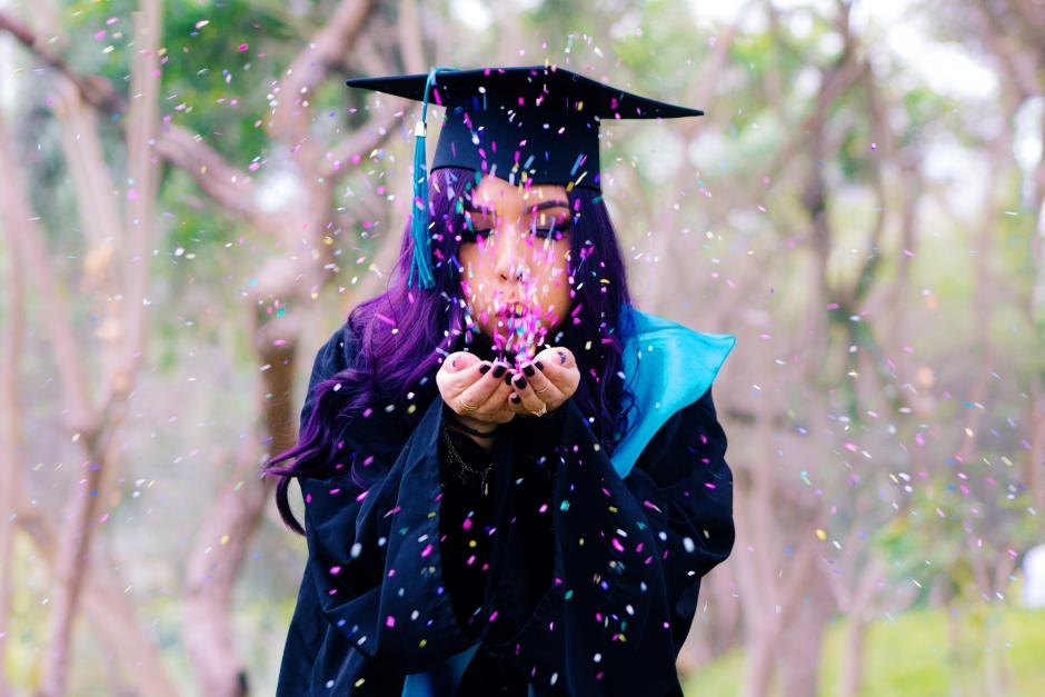 Graduating  Student girl blowing confetti